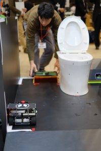 ゴミ吸引ロボットを設置中の田原さんとお掃除ロボット
